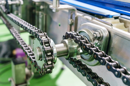Photo pour Gear and chain drive shaft in conveyor chain, and conveyor belt is on production line. - image libre de droit