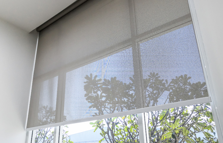 Foto de Roll Blinds on the windows, the sun does not penetrate the house. Window in the Interior Roller Blinds. Beautiful Blinds on the Window, the Sun and Heat Protection, the Perfect Windows Interior Decor - Imagen libre de derechos