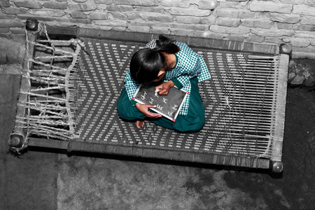 Foto de Elevated view of elementary age cheerful School girl of Indian Ethnicity sitting  on cot holding chalkboard wearing school uniform. She is writing alphabet on the chalkboard while sitting on the cot. - Imagen libre de derechos