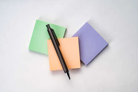 Top view of sticky note with pen on white background
