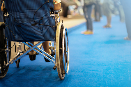 Photo pour Back view of woman on wheelchair during in in exhibition hall - image libre de droit