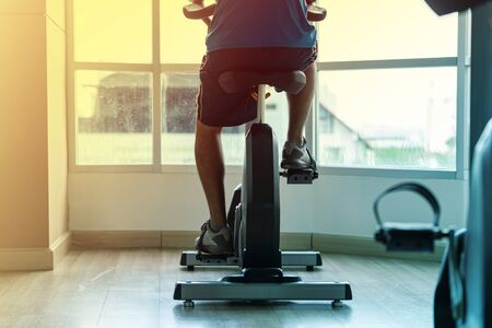 Photo pour Close up of a man exercise in gym, Cycling on bike in fitness gym - image libre de droit