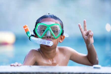 Photo for View of boy with swim glasses floating in the swimming pool - Royalty Free Image