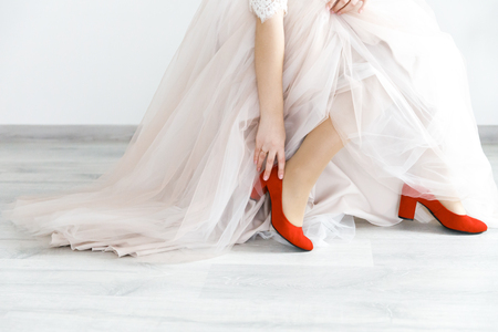 Photo pour The bride sits red elegant shoes before the wedding ceremony. - image libre de droit