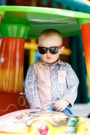 Photo pour Little cute boy is having fun playing on a big toy car - image libre de droit