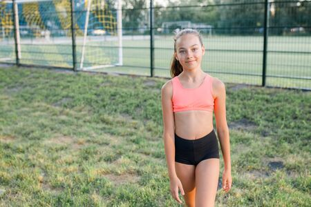 Photo for Young pretty girl of a slim body building, dressed in a sports uniform, spends time on a sports ground. Lifestyle - Royalty Free Image