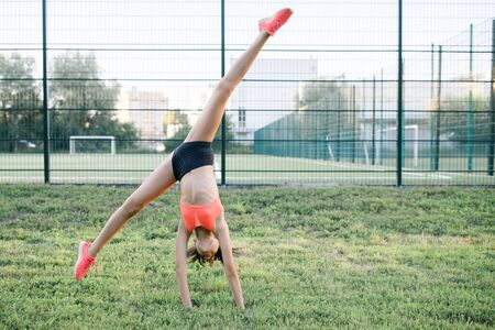 Photo for A young, sympathetic girl of slender body building, dressed in a form of sport, performs gymnastic exercises in the open air. Lifestyle - Royalty Free Image