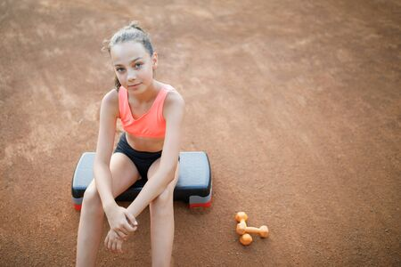 Photo pour A cute, pretty teenage girl sits on a step platform and relaxes after her workout on outdoor. Lifestyle - image libre de droit