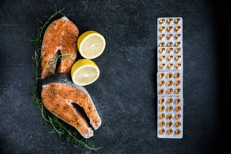 Photo pour Fresh salmon steaks lie on a dark background, alongside lemon and rosemary, a peppercorn with various types of peppers and vitamins for daily consumption. - image libre de droit