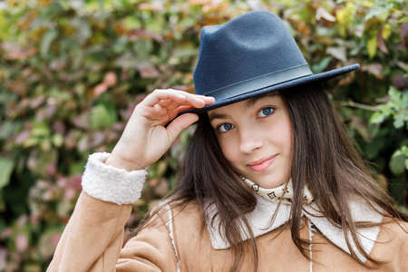 Photo pour Young teenage girl in a black hat stands on the street - image libre de droit
