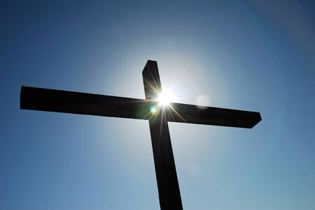 Cross against blue sky with bright sunburst at crossing of beams