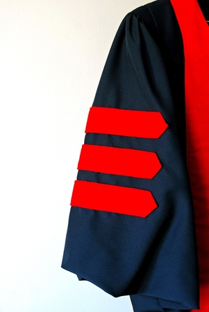 Sleeve of black graduation robe with three red doctoral stripes
