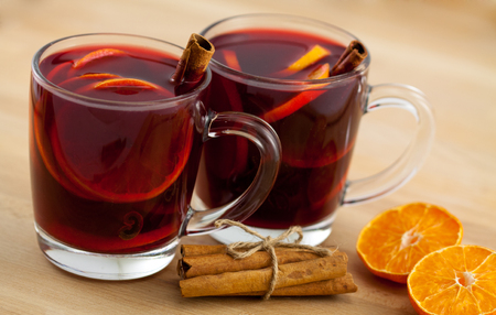 two mugs of mulled wine with cinnamon and orange