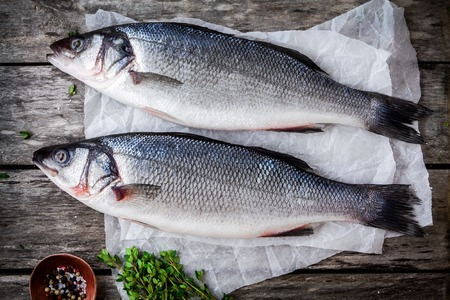 two raw seabass with fresh thyme on a rustic wooden table
