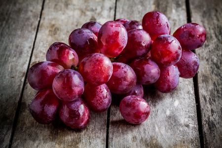 branch of ripe organic grapes on wooden rustic background