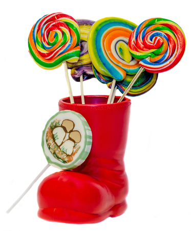 Santa Claus red boots, shoes with colored sweet lollipops, candys. Saint Nicholas boots with presents, gifts