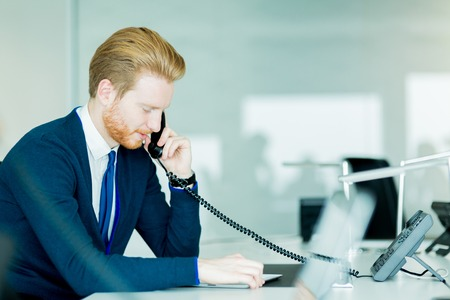 A handsome male, red haired worker in a call center office talking on a phone