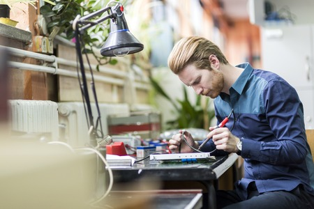 Photo pour Young handsome man soldering a circuit board and working on fixing hardware - image libre de droit