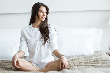 Foto de Beautiful brunette in a white shirt tailor seat posing on a bed and relaxing - Imagen libre de derechos