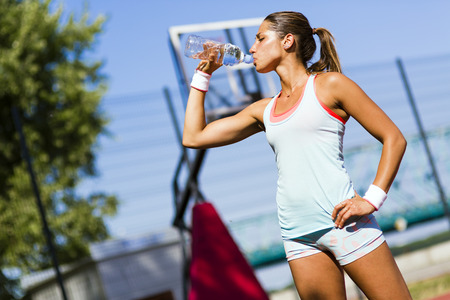 Young beautiful athlete drinking water after exercising to revitalize