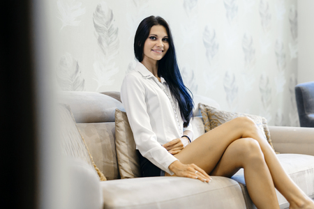 Elegant woman sitting on a sofa in a luxurious room and smiling