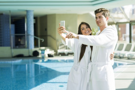 Couple in love standing next to a  pool in a  robe and relaxing