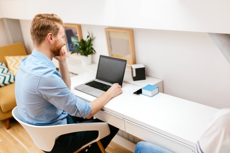 Photo pour Handsome self-employed business working from home on a laptop - image libre de droit