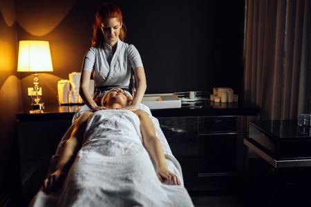 Massage therapist massaging beautiful brunette