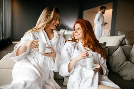 Women relaxing and drinking tea in robes during wellness weekend