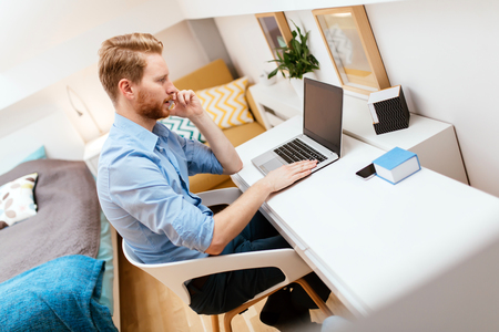 Photo for Handsome self-employed business working from home on a laptop - Royalty Free Image