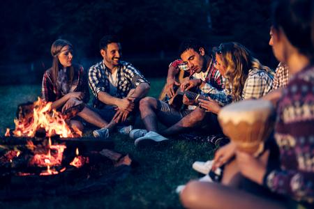 Friends enjoying music near campfire at night