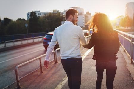 Photo pour Happy young couple walking hand in hand - image libre de droit