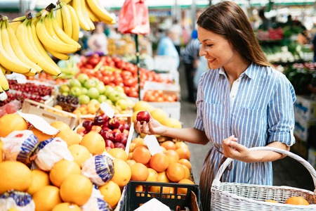 Photo for Picture of woman at marketplace buying fruits - Royalty Free Image