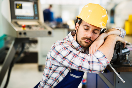 Photo pour Tired worker fall asleep during working hours in factory - image libre de droit
