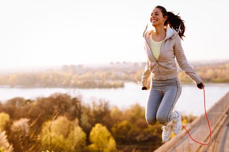 Foto de Active woman jumping with skipping rope outdoors - Imagen libre de derechos