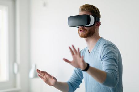Photo pour Man wearing virtual reality headset at home - image libre de droit