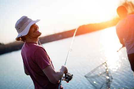 Photo pour Young man fishing on a lake at sunset and enjoying hobby - image libre de droit