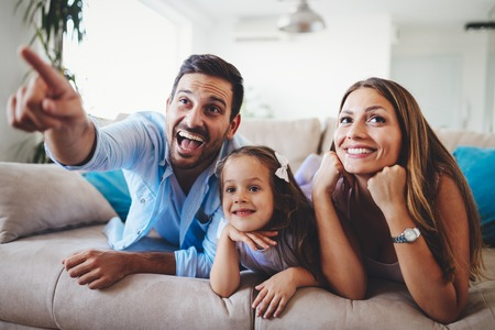 Photo pour Happy family watching television at their home - image libre de droit