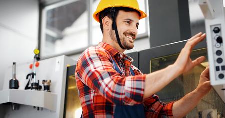 Foto de Industry Worker entering data in CNC machine at factory - Imagen libre de derechos