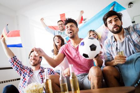 Photo pour Friends watching football game at home - image libre de droit