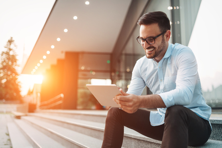 Foto de Portrait of businessman in glasses holding tablet - Imagen libre de derechos