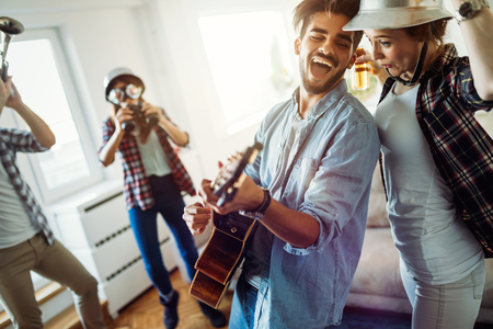 Photo pour Group of friends playing guitar and partying at home - image libre de droit