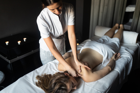 Foto de Young and healthy woman in spa salon. Traditional Swedish massage therapy - Imagen libre de derechos