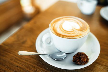 Foto de Cup with hot tasty coffee on wooden table in cafe, close up - Imagen libre de derechos