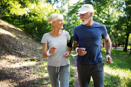 Photo for Mature couple jogging and running outdoors in city - Royalty Free Image
