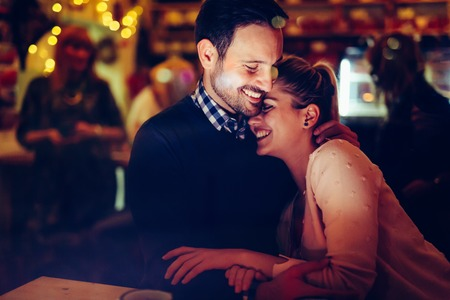Photo for Romantic couple dating in pub at night - Royalty Free Image