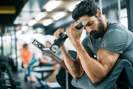 Foto de Strong ripped man training in modern gym - Imagen libre de derechos