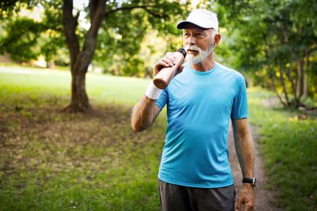 Photo pour Portrait of athletic mature man after run. Handsome senior man resting after jog at the park - image libre de droit