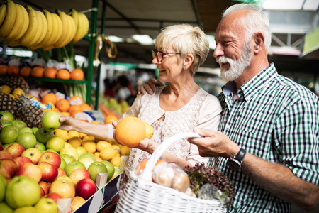 Photo pour Senior family couple choosing bio food fruit and vegetable on the market during weekly shopping - image libre de droit