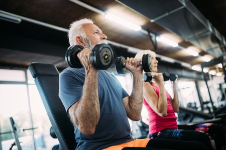 Photo pour Mature fit couple exercising in gym to stay healthy - image libre de droit